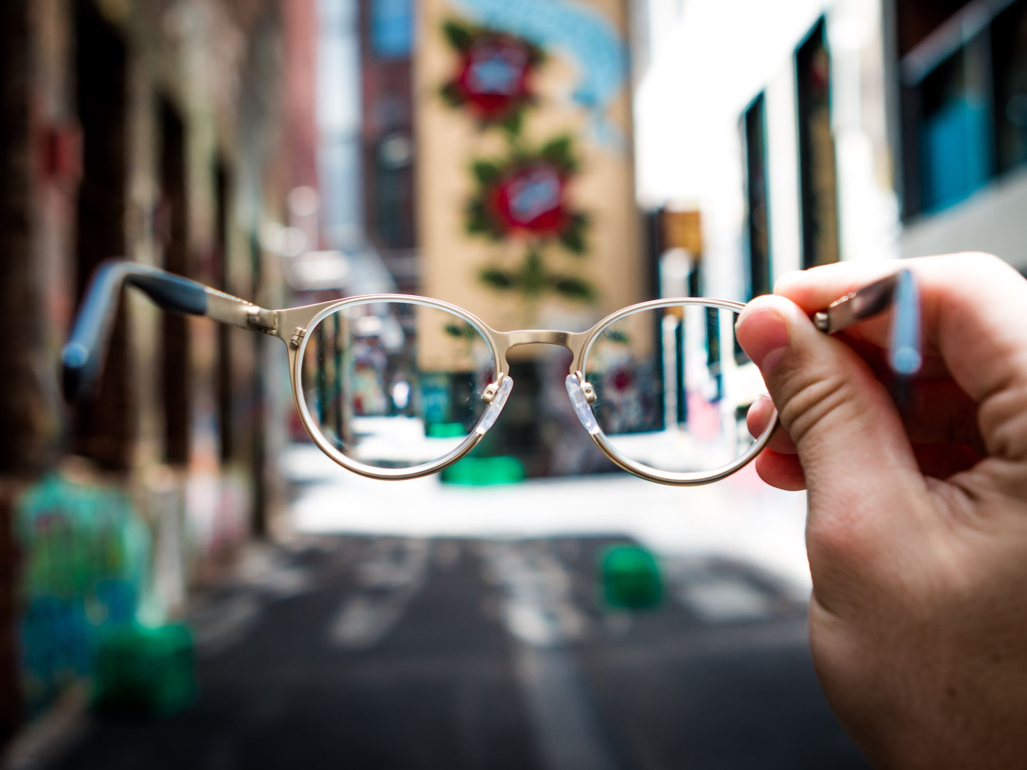 person holding a pair of prescription glasses against an urban backdrop