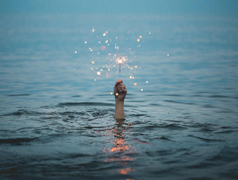 hand up from the sea holding a sparkler