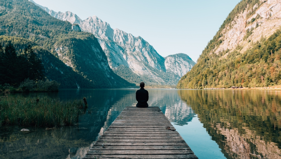 man sitting on a wooden pier over a lake looking at mountains in the background